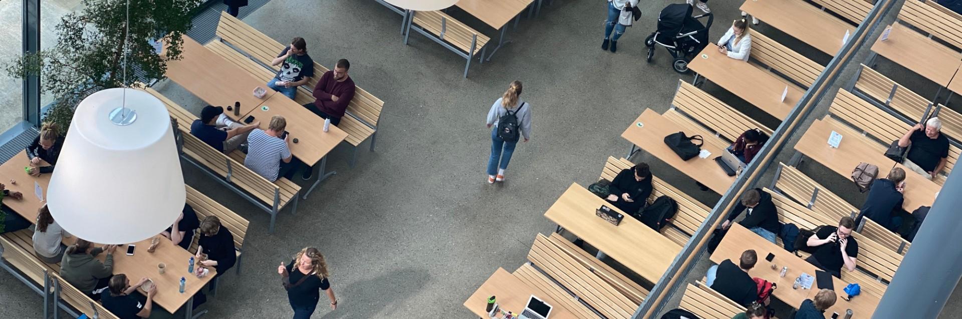 Oversiktsbilde over studenter som vrimler i atriet ved kafeen i Arne Rettedals hus