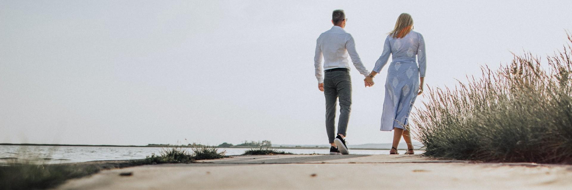 Et par som går tur på stranden (Foto: Unsplash)