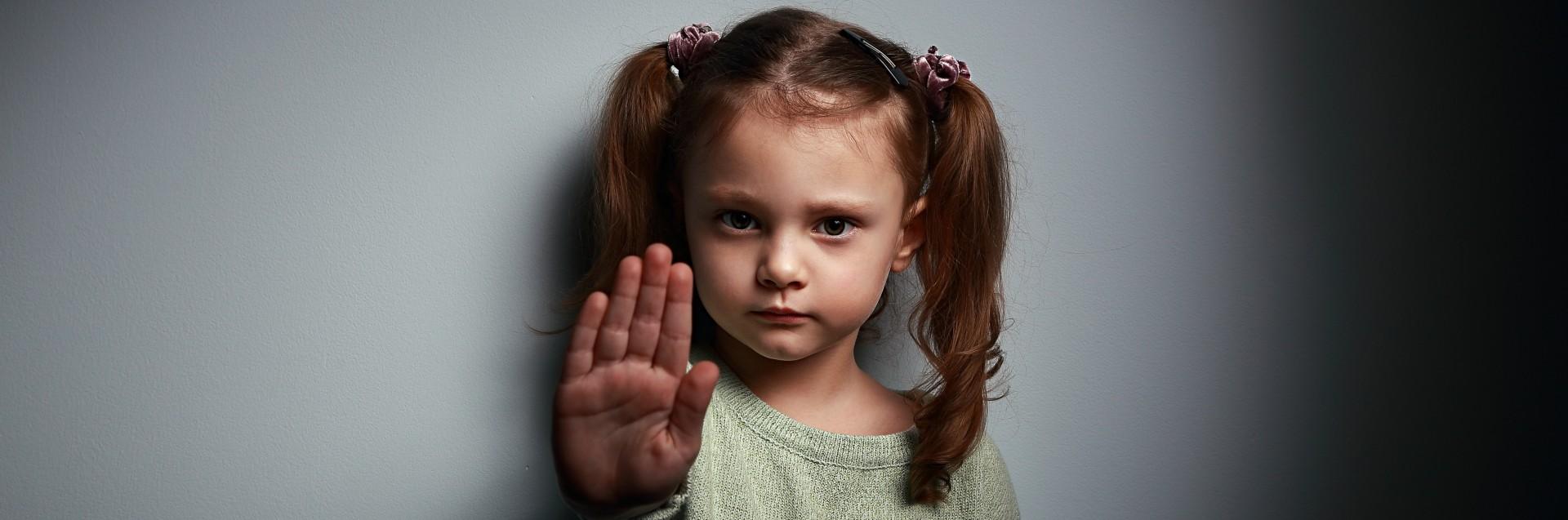 Liten jente som holder hånden foran seg for å vise at man skal stoppe