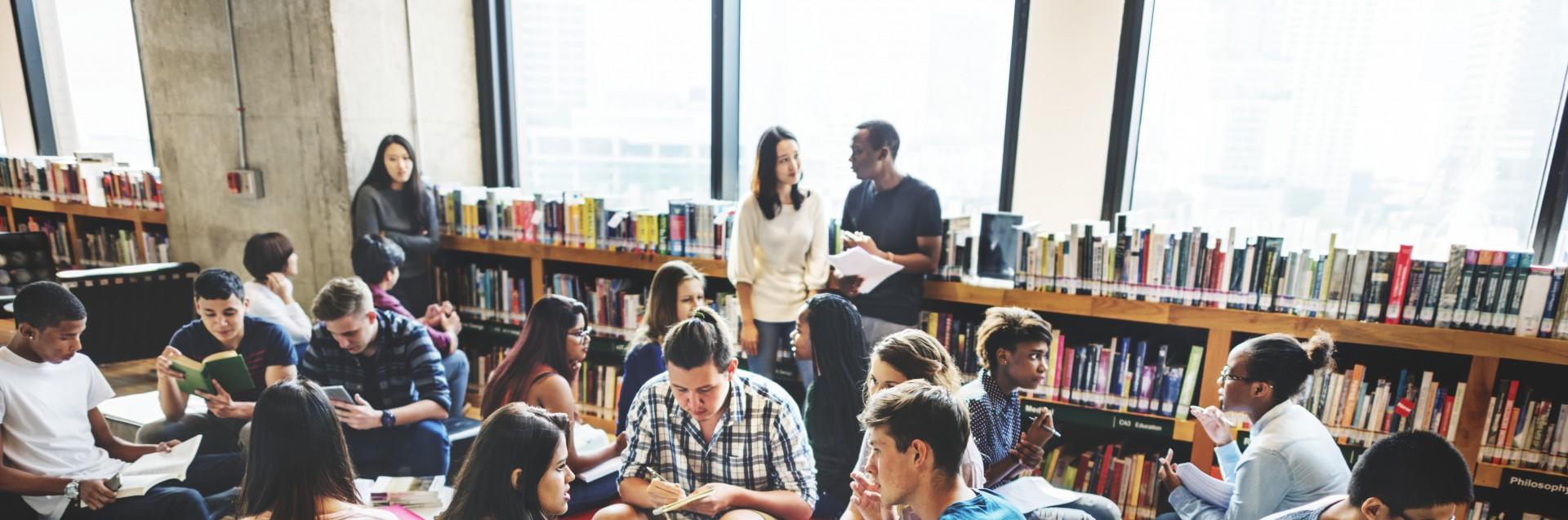Elever jobber i grupper i et rom med puffer. Lærer står i bakgrunnen og snakker med en av elevene.