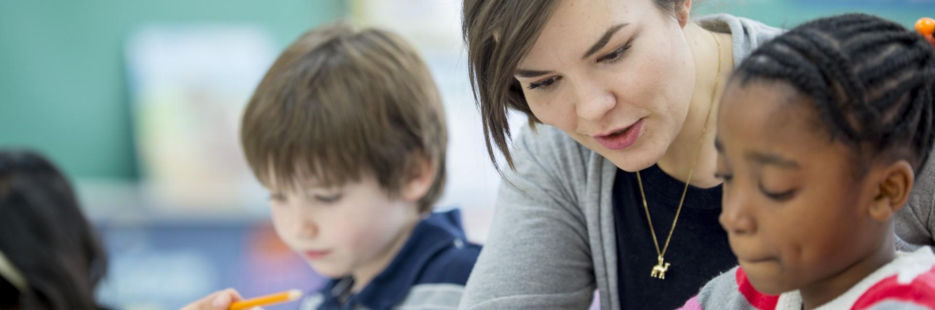 Klasseromsitasjon der lærer hjelper elev ved pulten.