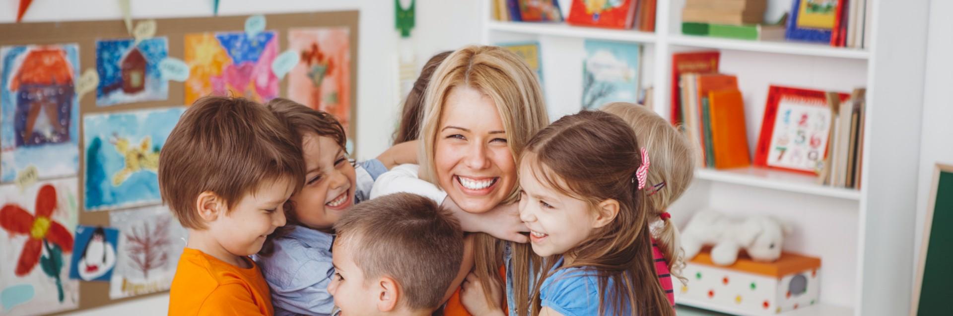 Seks barn klemmer en barnehageansatt