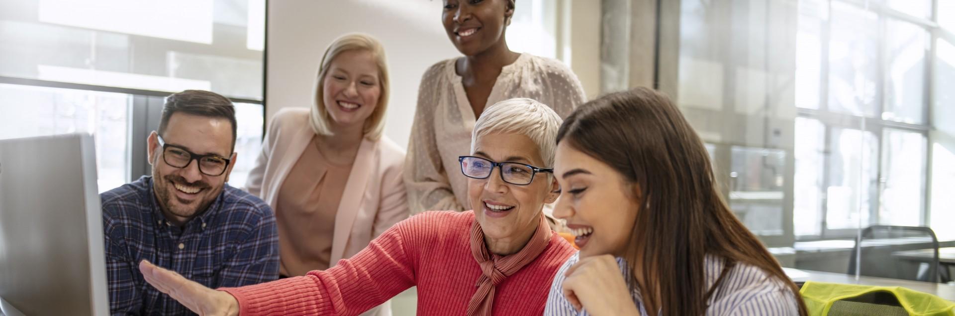 En gruppe lærere i forskjellig alder er samlet rundt en skjerm. Den eldste viser de andre noe. De følger interessert med.