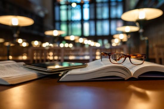 Bok oppslått i dunkel belysning med briller og nettbrett ved siden av