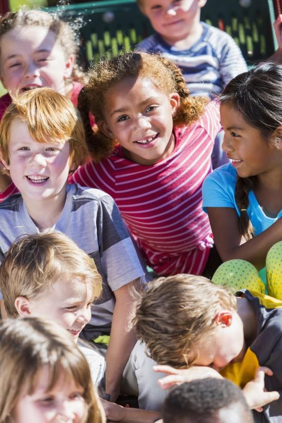 En gruppe av barn smiler til kamera
