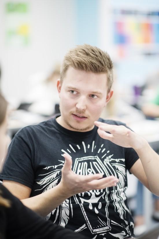 Mannlig lektorstudent forklarer noe for en elev i praksis