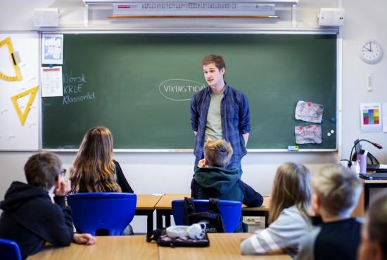 Mannlig lærerstudent står foran tavle og elever i klasserom