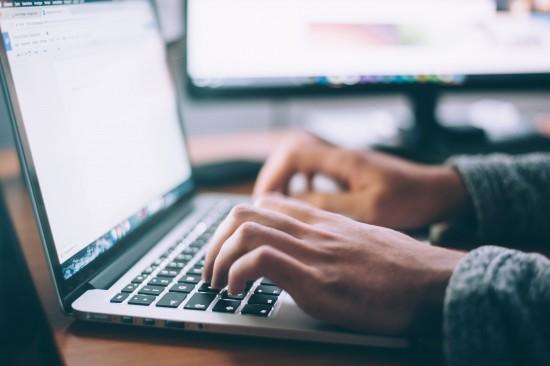 person skriver på laptop