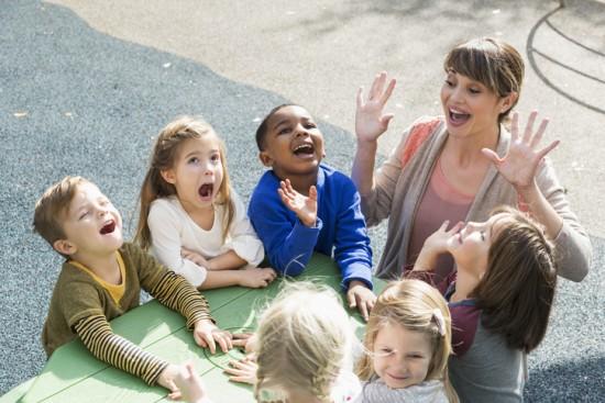Kvinnelig barnehagelærer er utendørs sammen med en gruppe barn