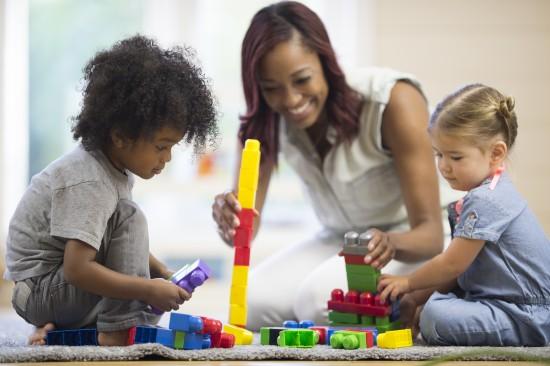 Kvinnelig barnehagelærer klipper og limer sitter på gulvet og bygger med klosser sammen med to barn