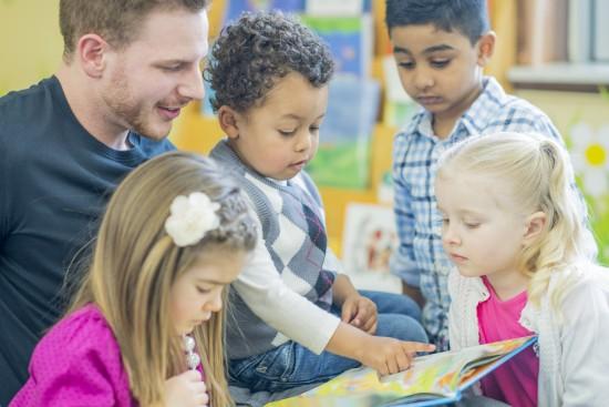 Mannlig barnehagelærer leser sammen med fire barn