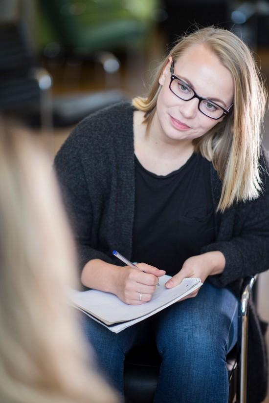 En kvinne sitter med penn og papir og ser på en person som sitter med ryggen til kameraet.