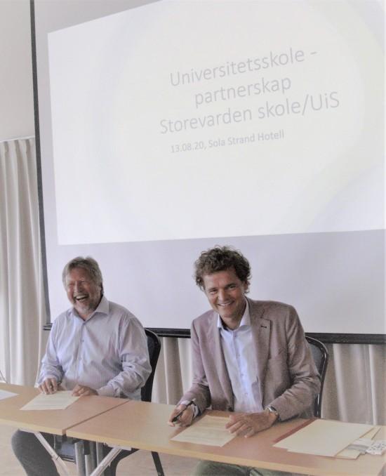 To menn smiler til kamera mens de signerer papirer