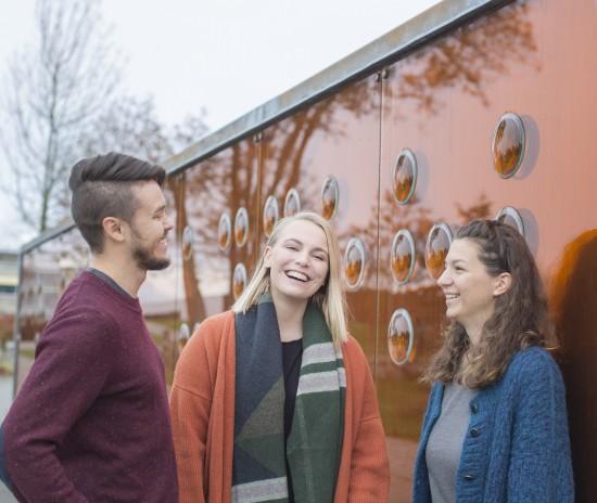 Glade studenter foran bronseveggen på Ullandhaug campus,