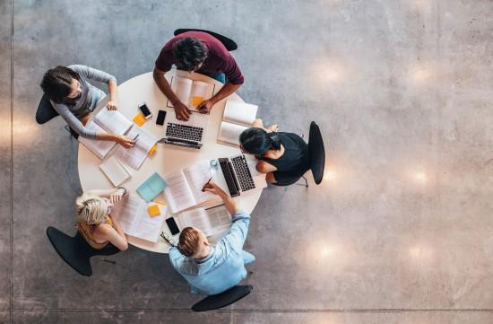 Bilde tatt ovenfra av fem studenter som sitter rundt et bord med bøker og pc og jobber/studerer..
