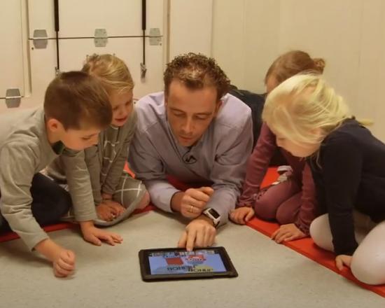 barnehagelærer og barn leser på ipad