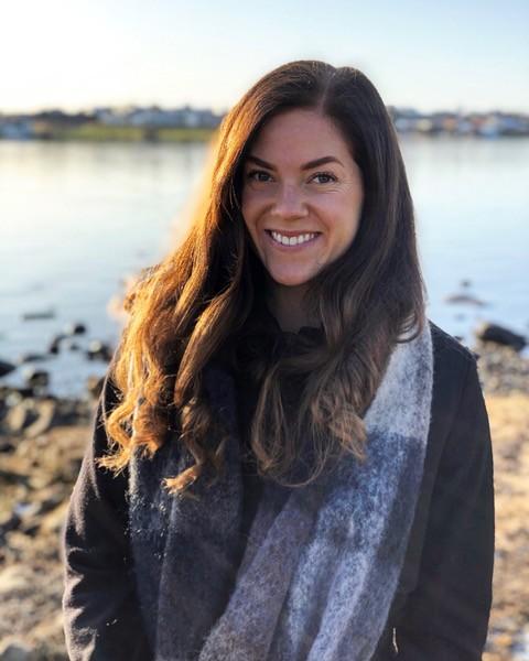 Kvinne med langt mørkt hår er ute i naturen, med en fjord i bakgrunnen