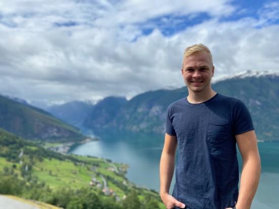 Mann med lyst hår står ute i naturen med fjord og fjell i bakgrunnen
