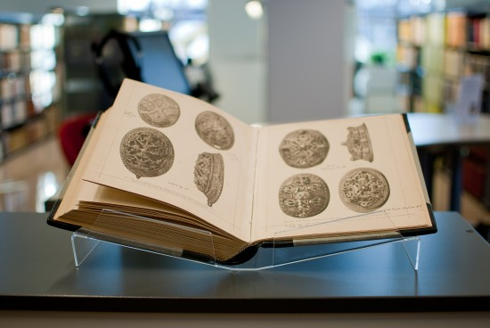 Åpen bok med bilder av arkeologiske gjenstander