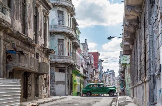 Gate med slitte, men fargerike hus i Cuba. Midt i gaten kjører en grønn bil.