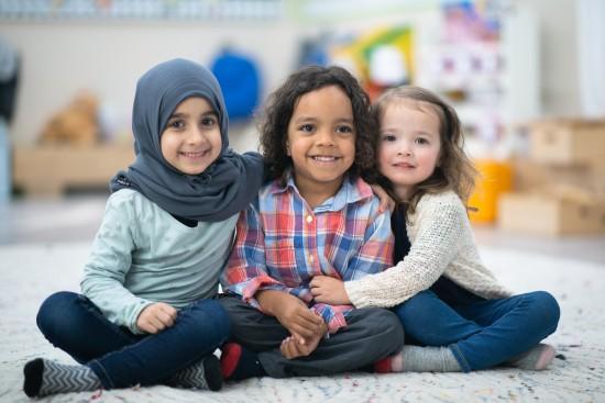 Tre små barn sitter ved siden av hverandre på gulvet og ser på fotografen