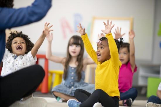 Barn sitter på gulvet og ser mot et felles punkt. De holder armene over hodet og munnene deres er åpne, som om de synger.