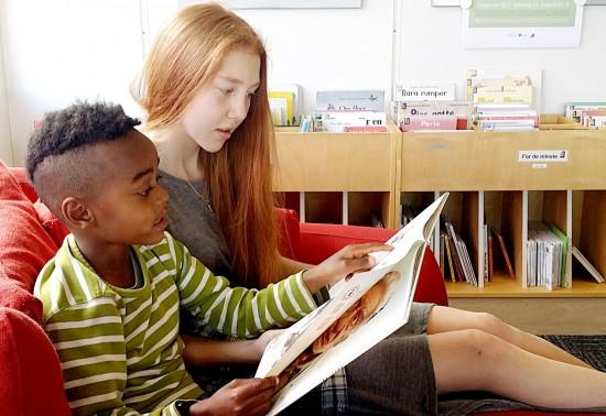Ungdomsskoleelev leser for førsteklassing
