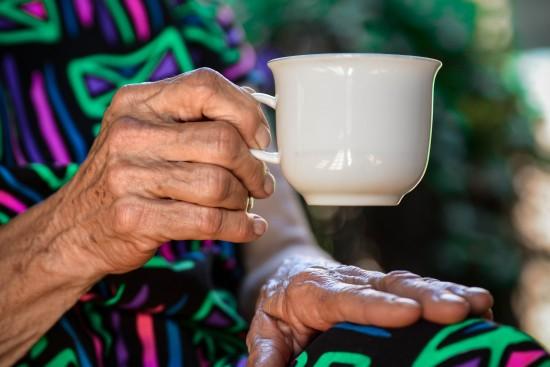 En eldre kvinne sitter og holder en kaffekopp.