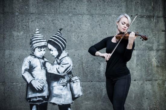 Kvinnelig fiolinist spiller i Stavanger sentrum foran grafitti