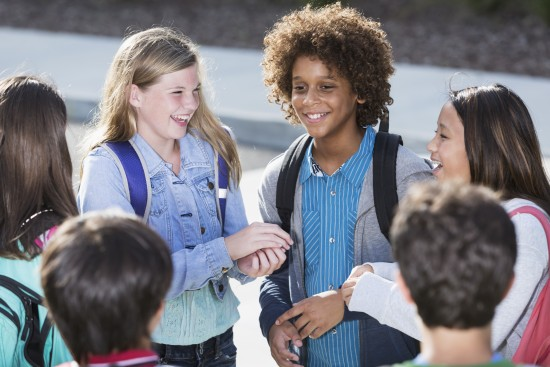 En gruppe elever står i ring og smiler.