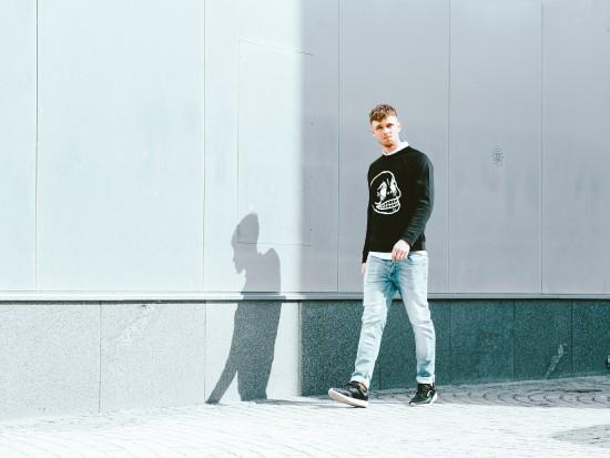 En ung mann kledd i jeans og svart genser går langs en vegg.