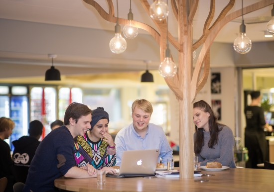 Engasjerte studenter rundt en PC i kantinen