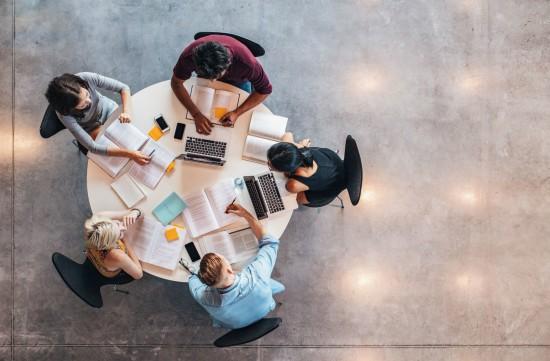 Frem studenter rundt ett bord sett ovenfra