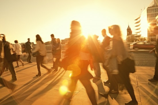 Mennesker går på gate, motlys fra solnedgang