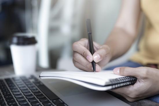 nærbilde av person som skriver i notatblokk