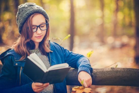 Jente leser i park. foto: Getty