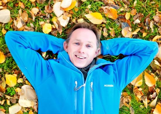 Professor Lutz Eichacker ligger på gresset med løv rundt