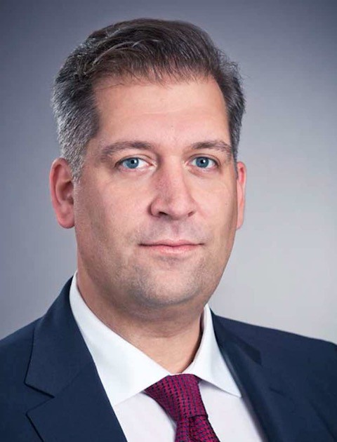 Associated professor at the University of Stavanger, and project leader Thomas Michael Sattich. A middle-aged man with dark hair with hints of grey, eye contact, blue eyes and suit. White shirt with a pink-burgundy colored tie with blue crosses.