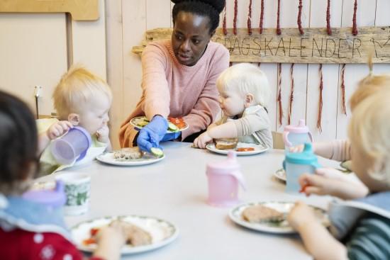 En ansatt i en barnehage hjelper barna med maten.