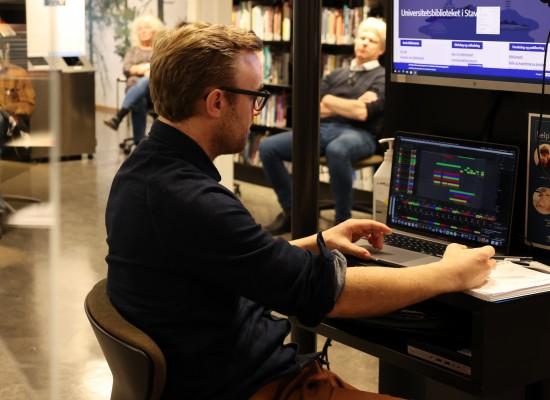 Kristoffer Berre Alberts sitter foran pc på et bibliotek