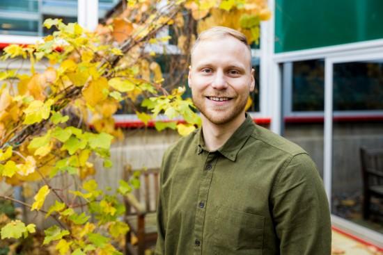 Trond Olav Hågbo i atrium med tre i bakgrunnen