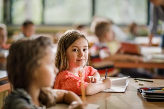 jente skriver i klasserommet