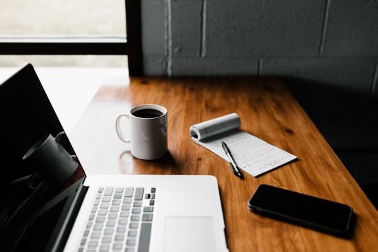Et bord med en laptop, mobil, kaffe og notatblokk - illustrasjon på studiehverdag