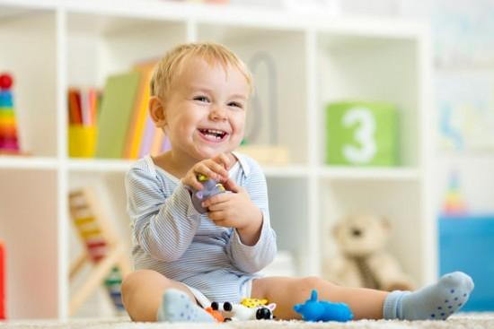 Barn sitter på gulvet med leke i hendene. Hylle med leker i bakgrunnen.