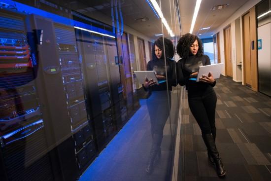 Kvinne med laptop i datarom
