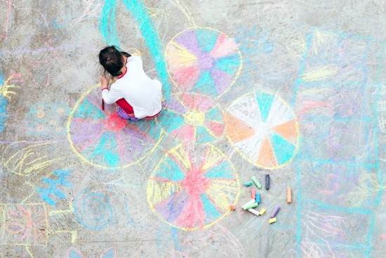 barn tegner med kritt i skolegården