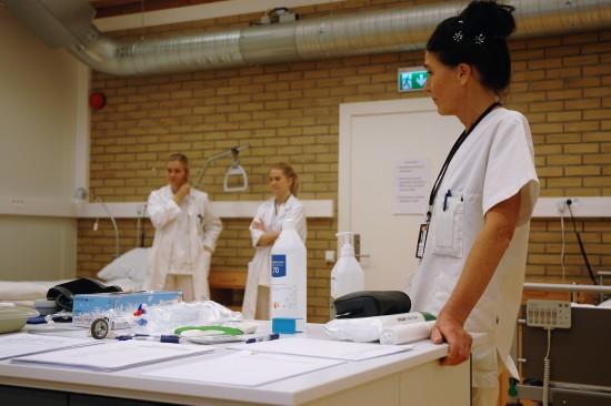 Lærer og studenter i sykepleielaben