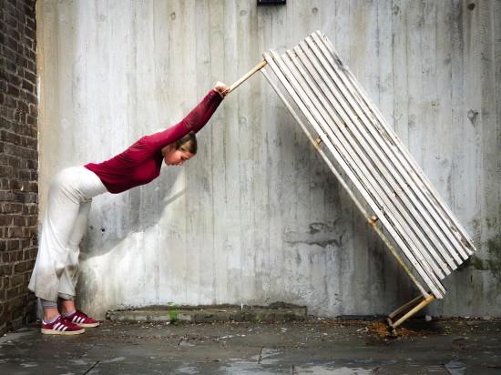 Rød- og hvitkledt danser løfter hvit parkbenk på høykant