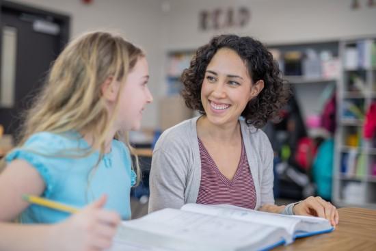 Lærer og elev ser smilende på hverandre.