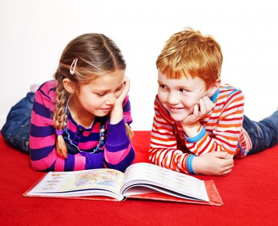 to barn leser bok på gulvet